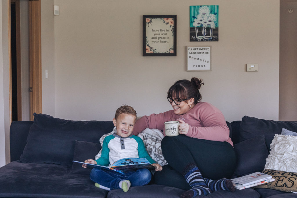 Shannon and her son cozy up on the couch with coffee and a good book.