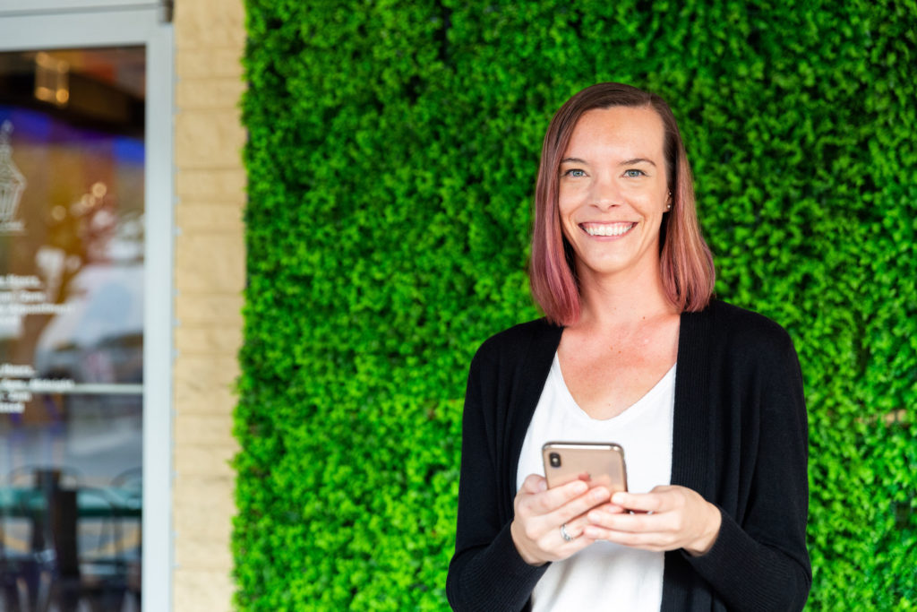 Ashley Erickson, account manager of Alyssa Gay Consulting, stands in front of a greenery wall with her phone in hand.